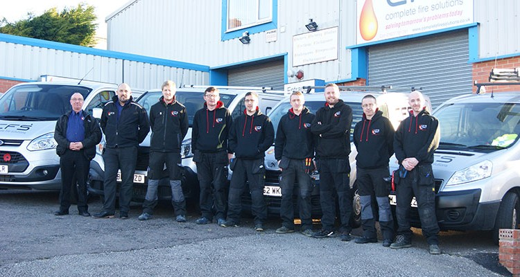 The team at Complete Fire Solutions stood in fron tof the van fleet.